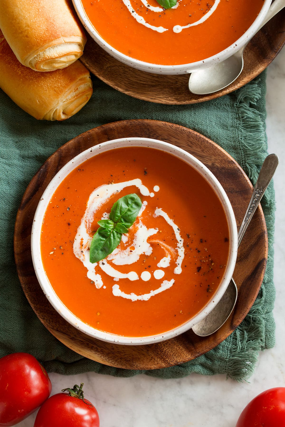 Overhead image of serving of tomato soup swirled with heavy cream.