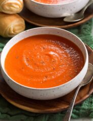 Single serving of tomato soup shown in a white bowl set over a wooden plate.