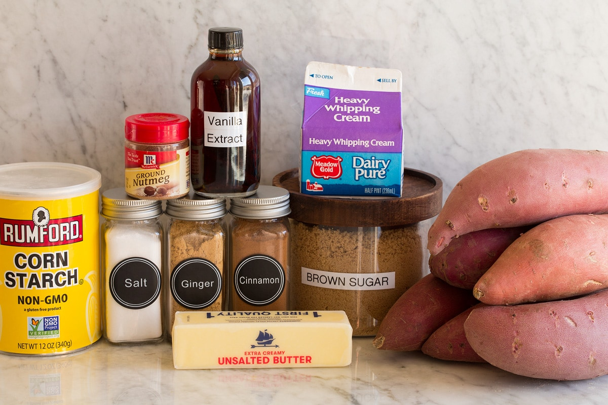 Image of ingredients used to make candied yams. Includes sweet potatoes, brown sugar, cream, butter, cinnamon, nutmeg, ginger, salt, vanilla and cornstarch.