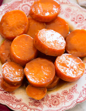 Close up image of candied yams on a red and white decorative side plate.