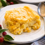 A single serving of corn casserole presented on a white plate with a spoon on the side.