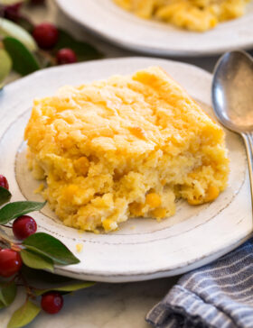 Single serving of corn casserole shown on a white plate with a spoon to the side.