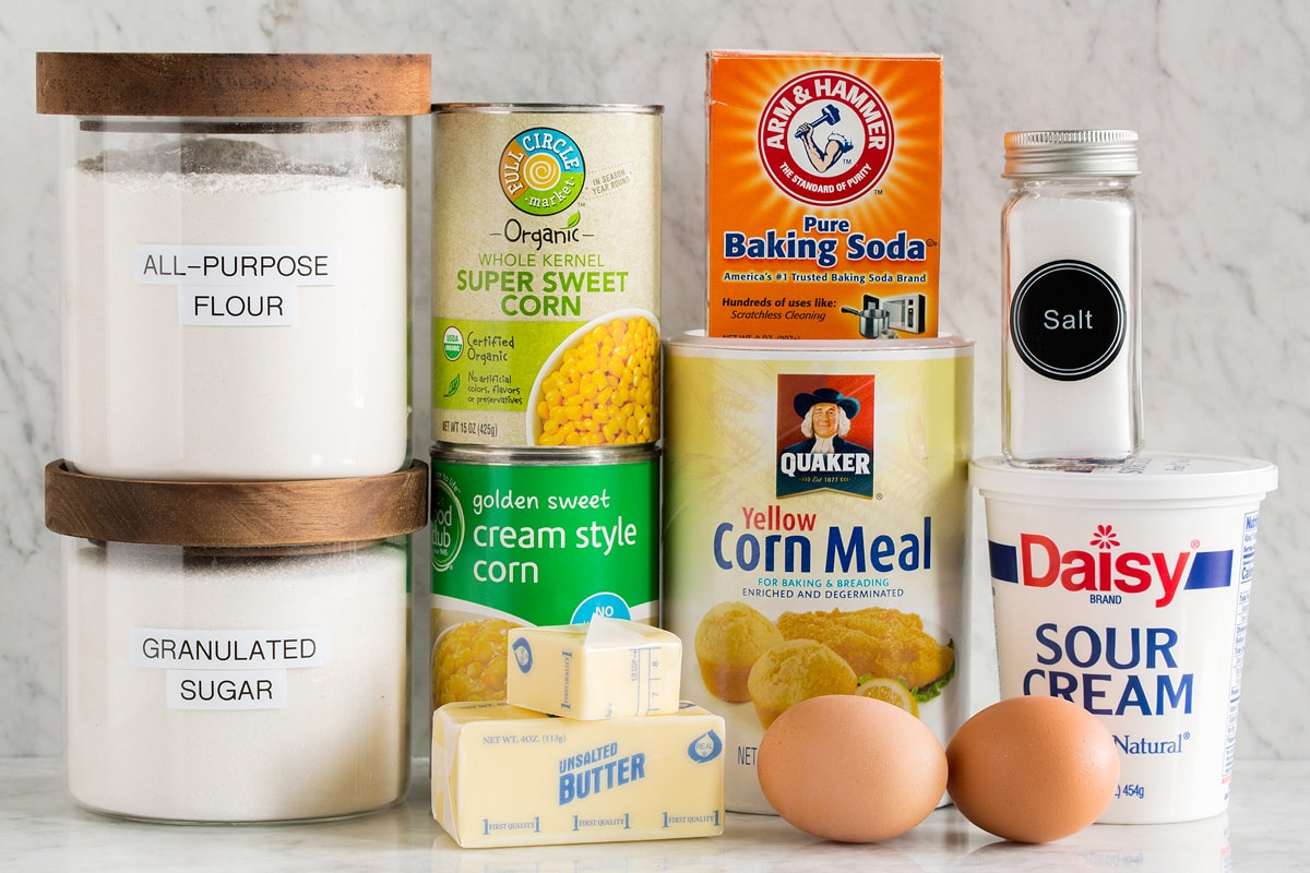 Picture of the ingredients needed to make a corn casserole from scratch.  Includes canned and creamed corn, flour, sugar, baking soda, sour cream, cornmeal, salt, eggs and butter.
