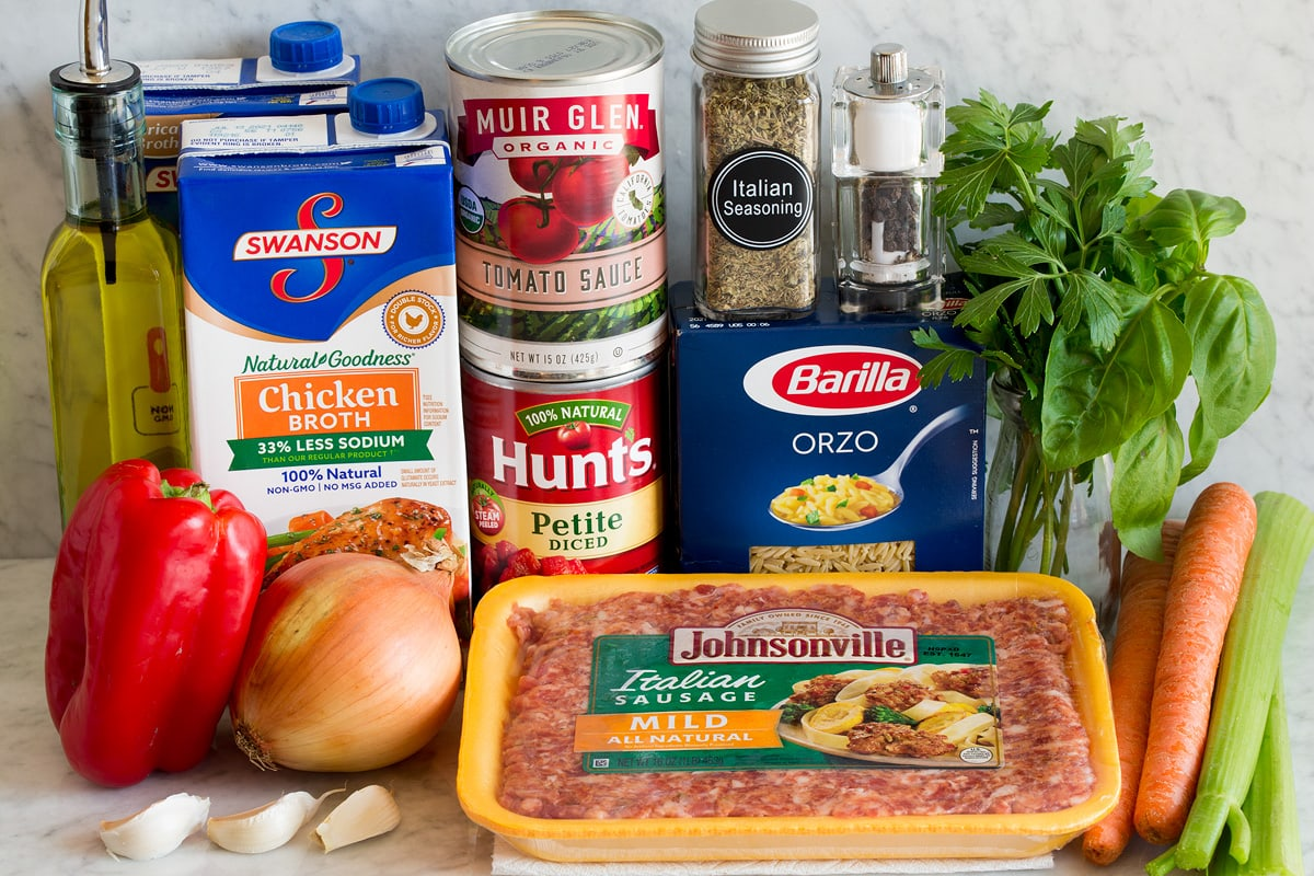 Image of ingredients used to make Italian sausage and orzo soup. Includes mild Italian sausage, orzo, carrots, celery, basil, parsley, Italian seasoning, salt and pepper, tomato sauce, diced tomatoes, chicken broth, yellow onion, bell pepper, olive oil and garlic.