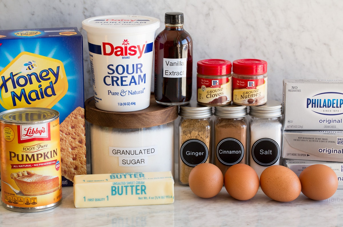 Image of ingredients needed to make pumpkin cheesecake. Includes graham crackers, sugar, butter, cream cheese, eggs, pumpkin, spices, sour cream and vanilla.