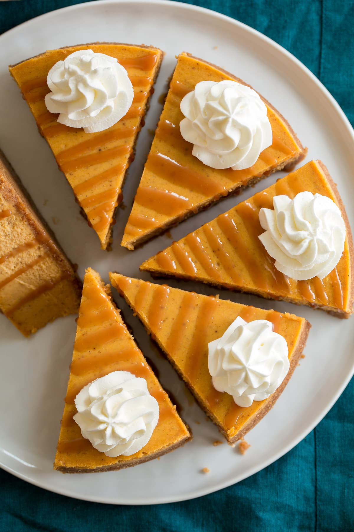 Overhead image of six slices of pumpkin cheesecake on a white serving platter.