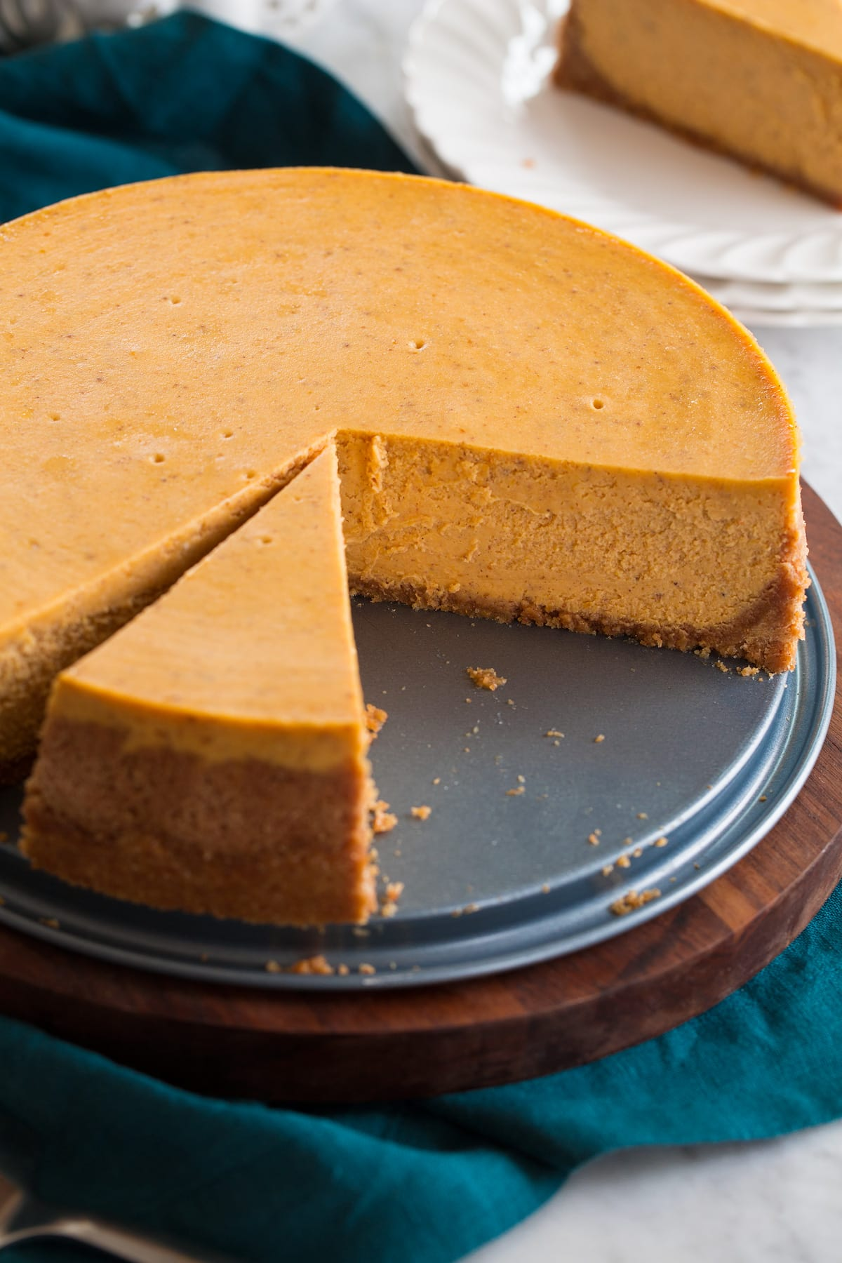 Nearly whole pumpkin cheesecake shown on a platter with a slice cut.