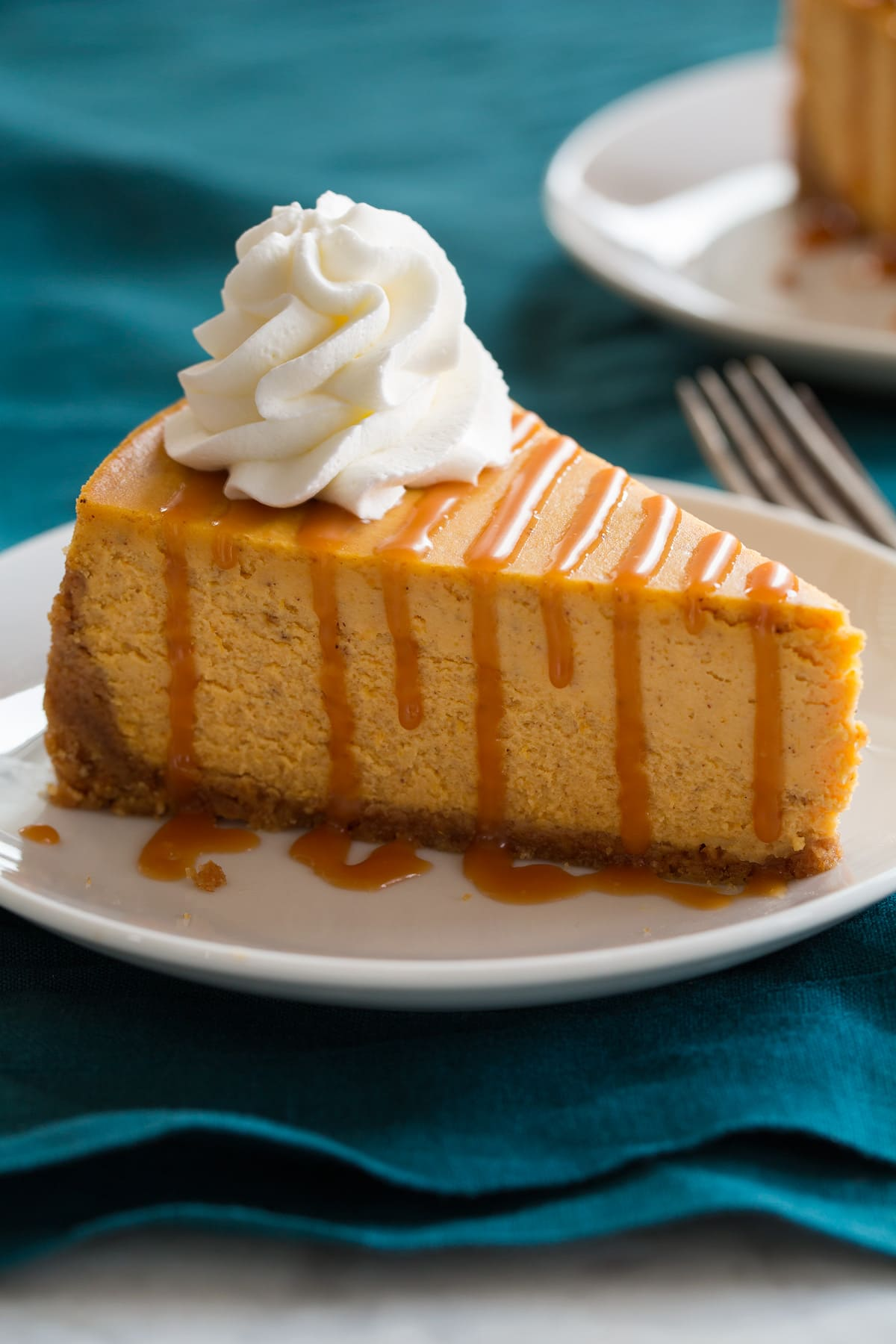 Close up image of slice of pumpkin cheesecake that is topped with caramel sauce and whipped cream.