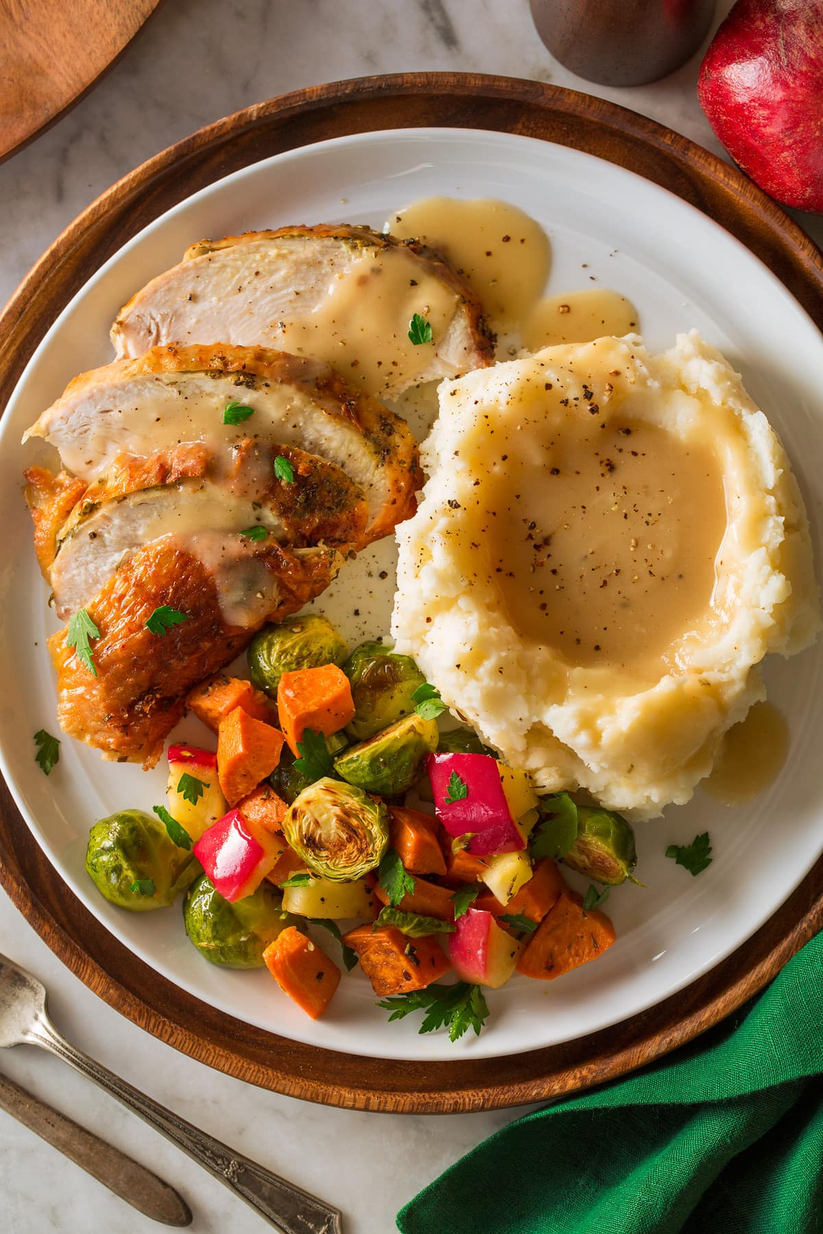 Roast Turkey Breast on a platter with a side of mashed potatoes and roasted vegetables.