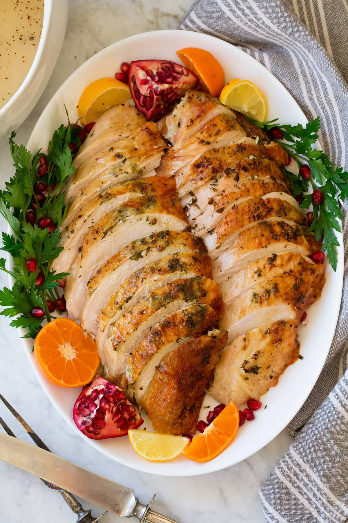 Overhead image of sliced Roast Turkey Breast on a white oval platter with decorative fruit and herbs.