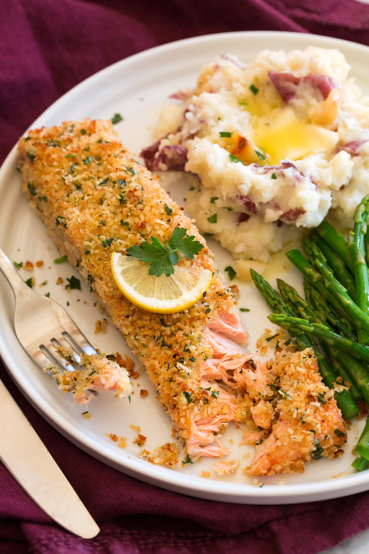 Baked salmon with parmesan and panko breadcrumb coating shown served on a plater with asparagus and garlic mashed potatoes.