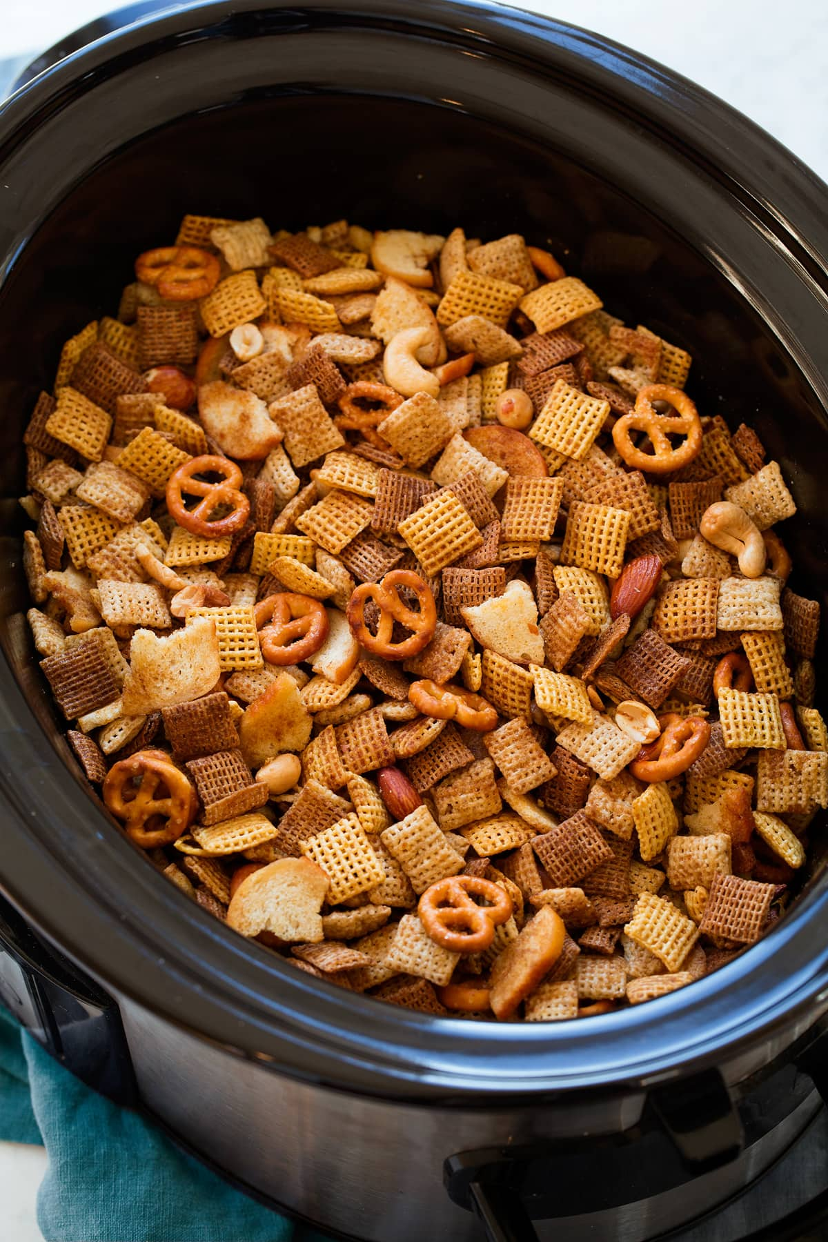 Chex Mix in a slow cooker shown after cooking.