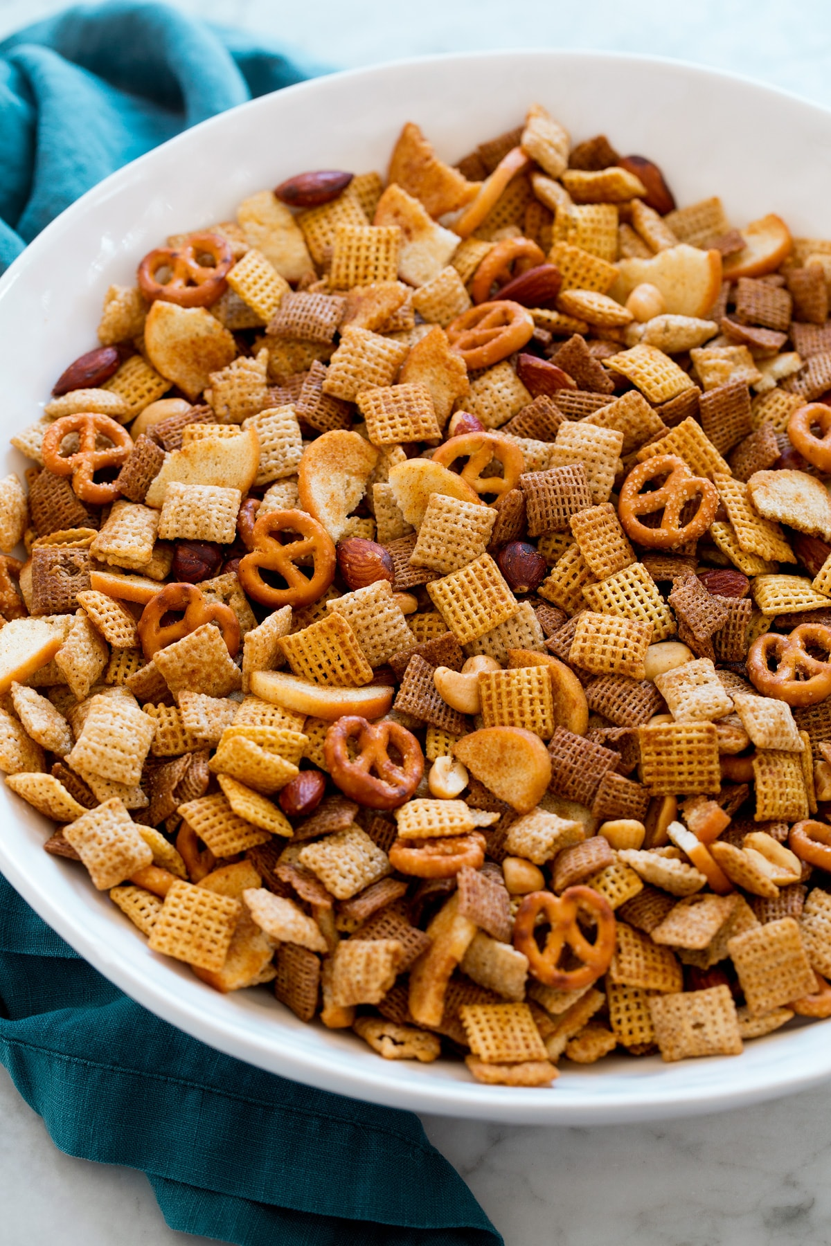 Homemade Chex Mix shown from a side angle in a large white serving bowl.