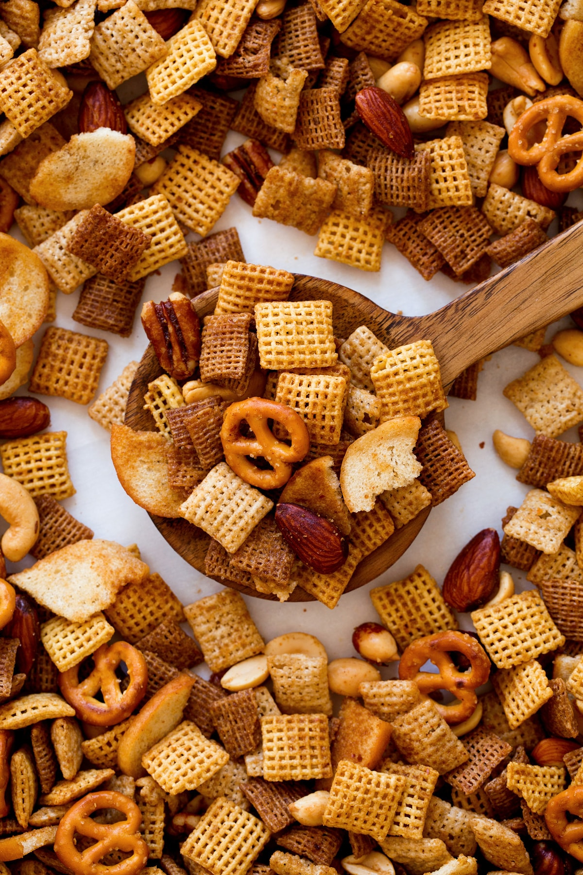 Wood spoon full of Chex Mix shown close up.