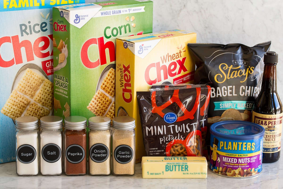 Image of ingredients used to make Chex Mix. Shows rice, corn and wheat Chex cereal, bagel chips, Worcestershire sauce, mixed nuts, pretzels, butter, and spices in jars.