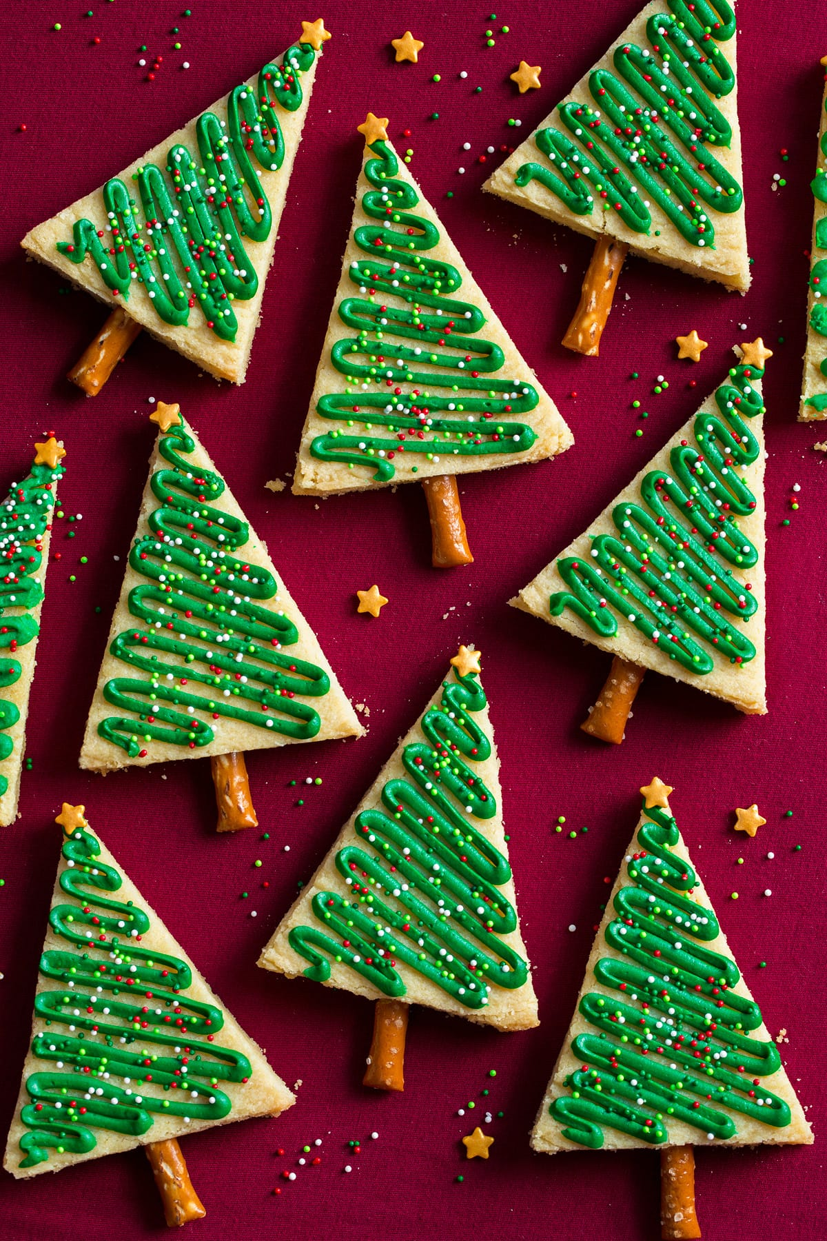 Triangular decorated Christmas tree cookies shown on a red surface.
