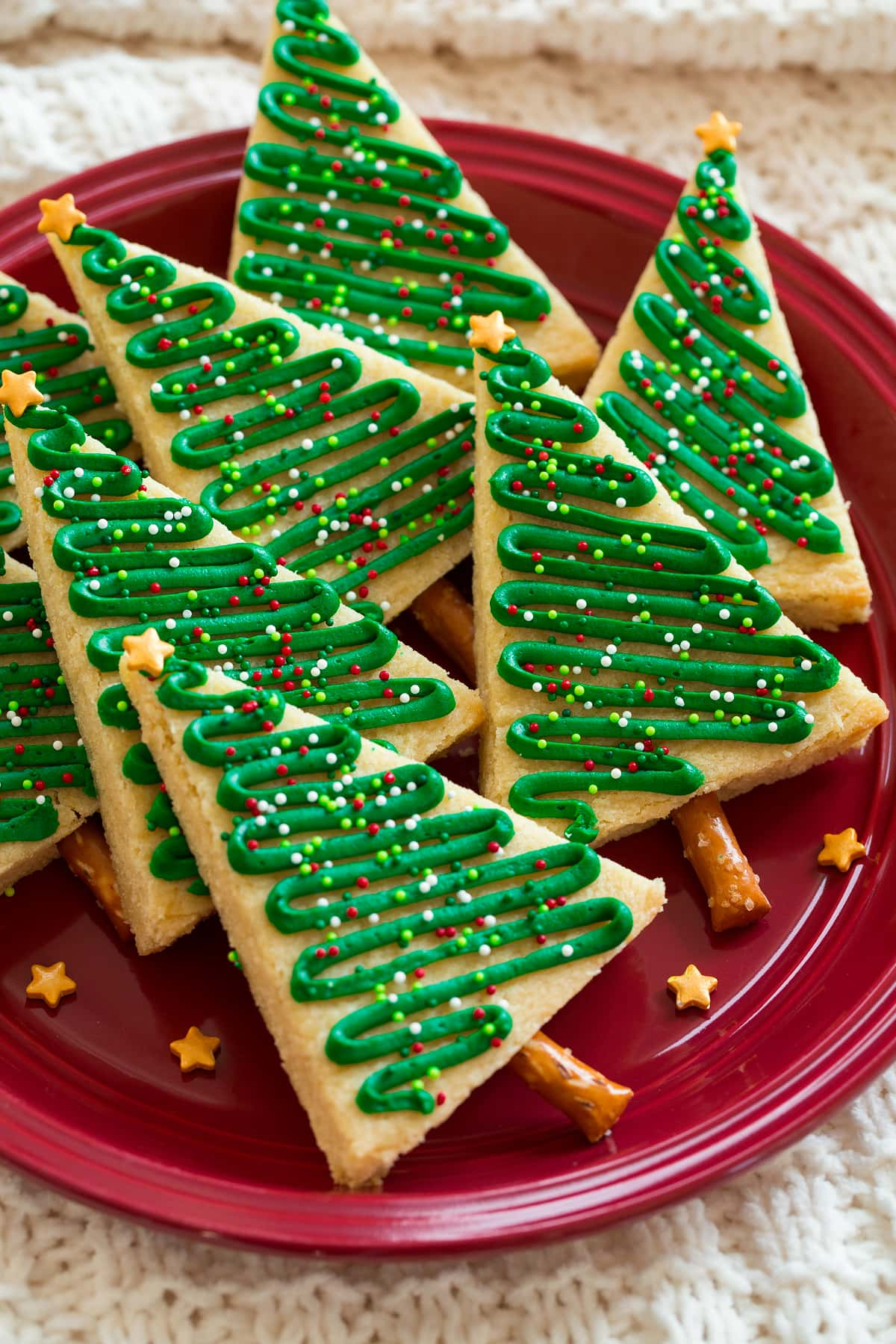 Christmas tree cookies shown on a red plate.