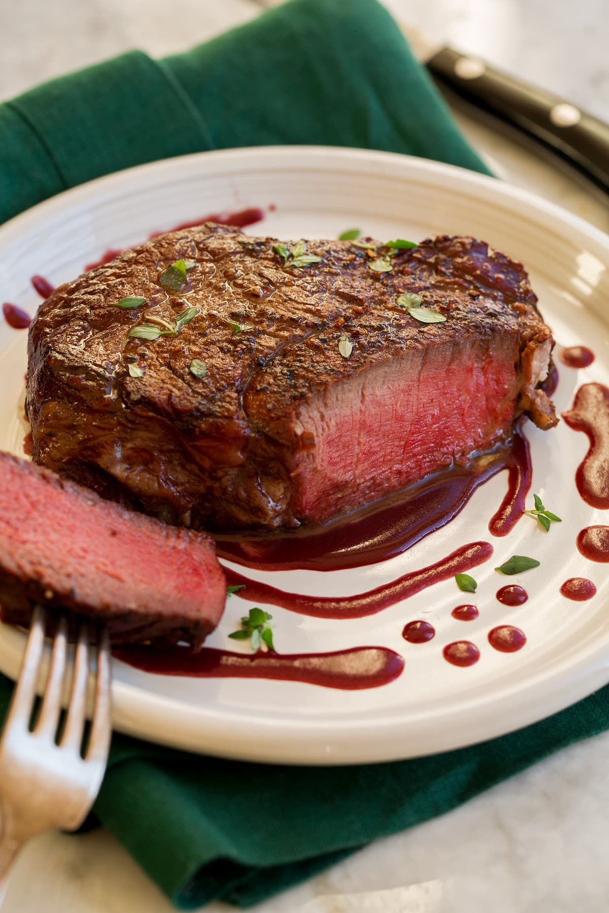 Filet Mignon on a serving plate with red wine sauce.