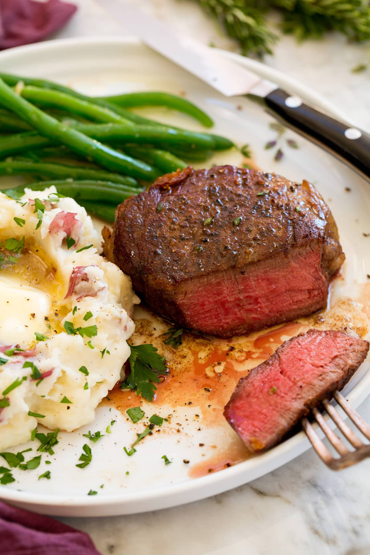 Filet Mignon shown on a serving plate with a side of mashed potatoes and steamed green beans.