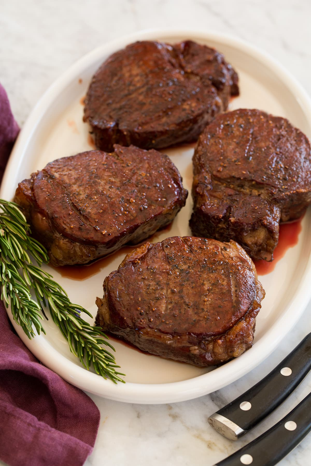 Four cooked fillet mignon steaks on a serving platter.