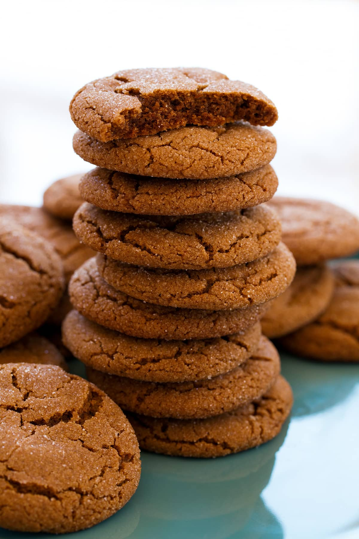Tall stack of molasses cookies with the top cookie broken in half to show soft moist texture of interior.