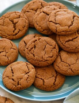 Molasses cookies layered on a blue plate.