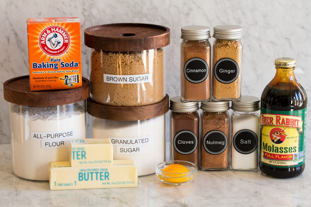 Image of ingredients used to make molasses cookies. Includes flour, sugar, molasses, brown sugar, baking soda, salt, egg yolk, butter, cinnamon, nutmeg, ginger, and cloves.
