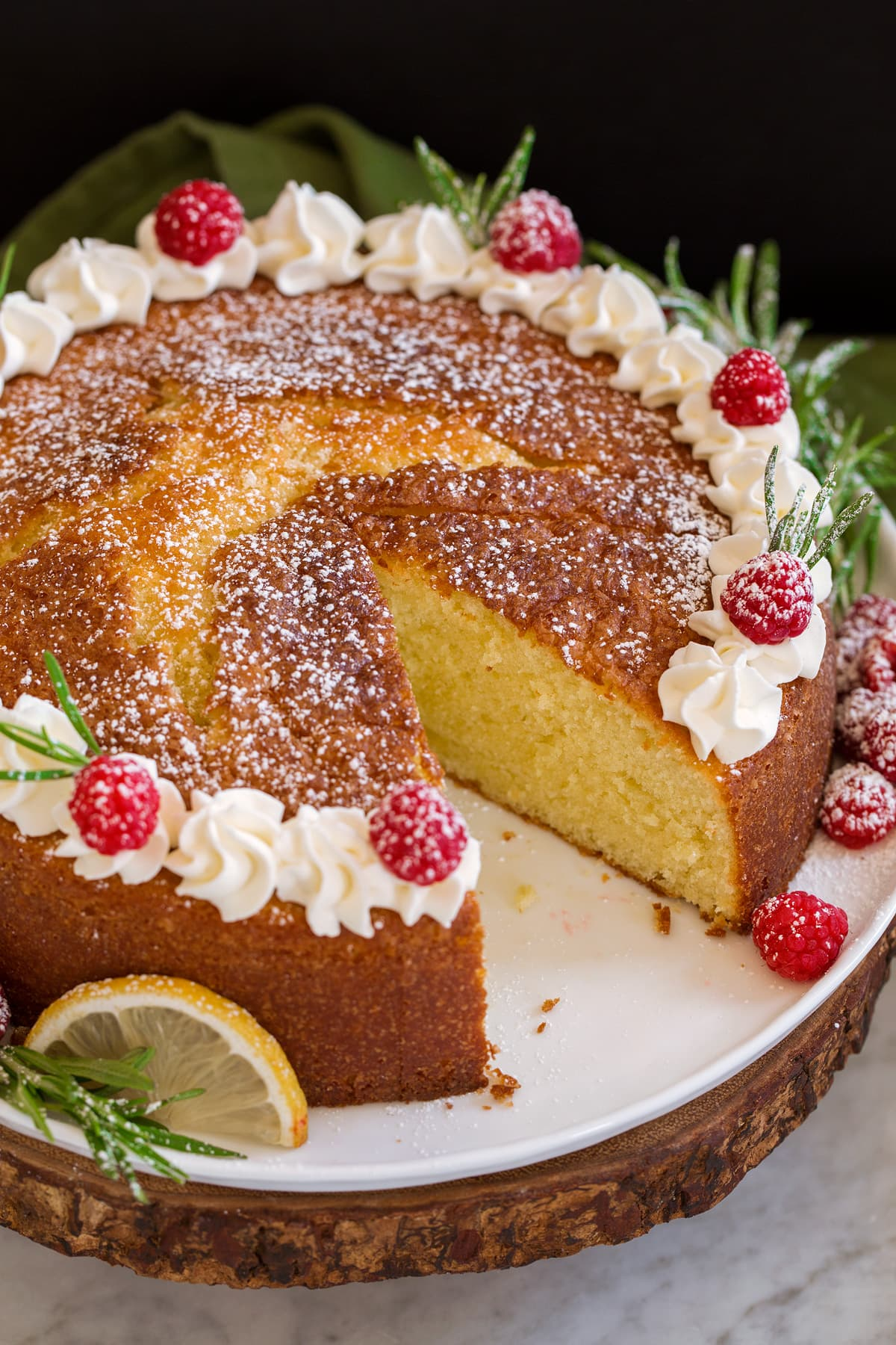 Photo of whole olive oil cake with one slice removed.
