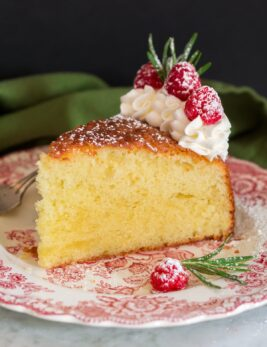 Photo of slice of olive oil cake decorated with whipped cream, raspberries and rosemary. Shown on a decorative red plate.