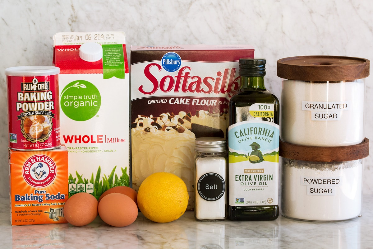 Photo of ingredients used to make olive oil cake. Includes cake flour, baking powder, baking soda, salt, eggs, lemon, extra virgin olive oil, milk, granulated sugar and optional powder sugar.