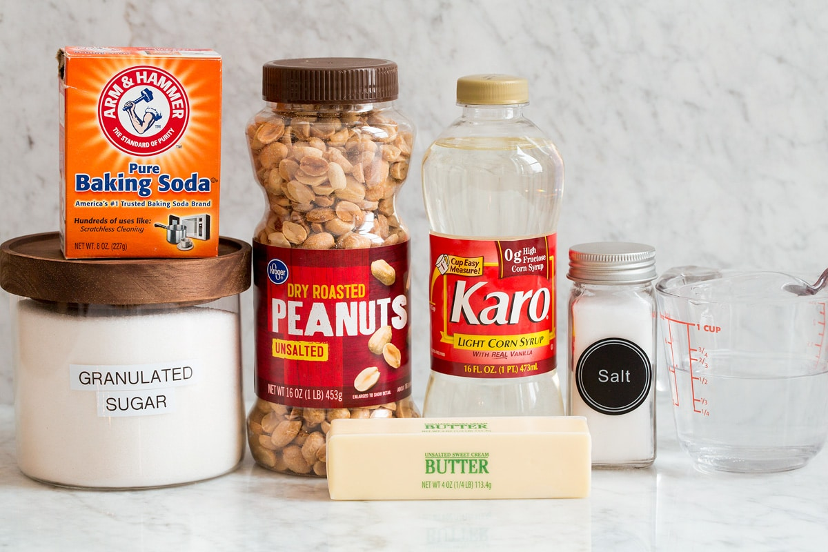 Photo of ingredients used to make peanut brittle. Includes sugar, baking soda, peanuts, butter, corn syrup, salt and water.