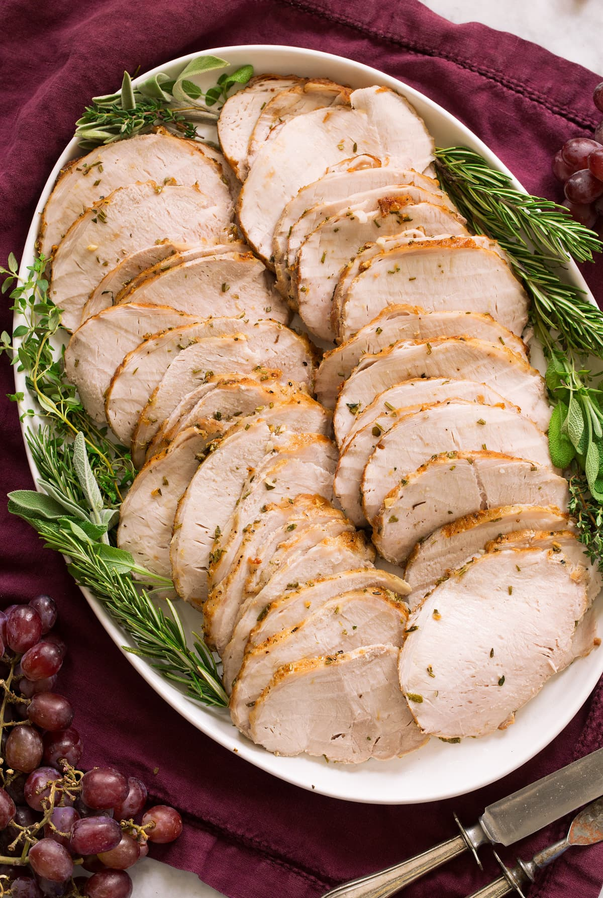 Pork loin shown cooked and thinly sliced on a white oval serving platter over a purple cloth.