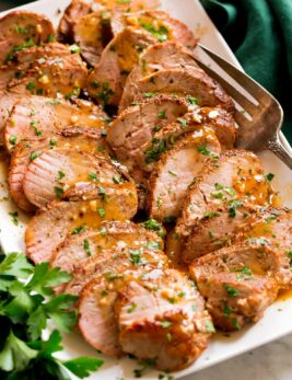 Sliced baked pork tenderloin on a platter with pan sauce.