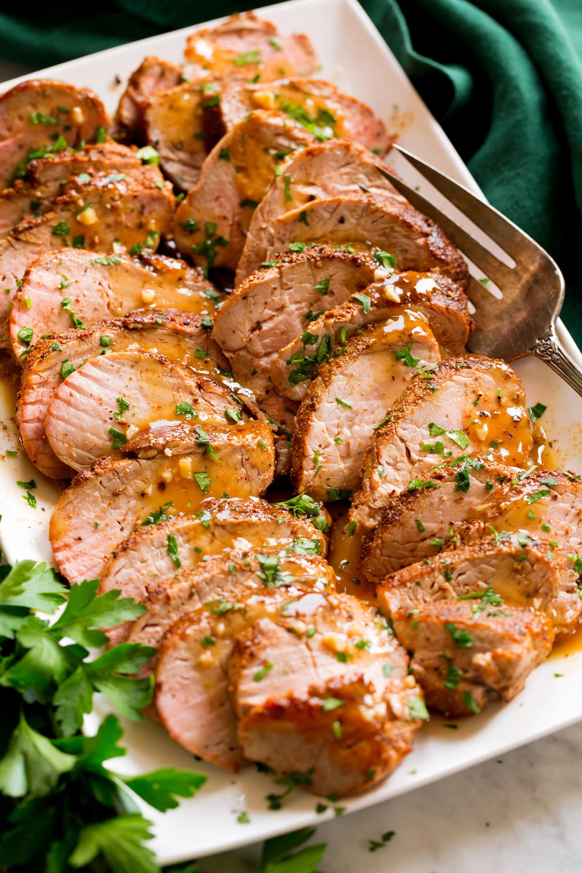Baked Pork Tenderloin sliced into strips resting shown on a platter. Pork is rubbed with spices, topped with a pan sauce and parsley.
