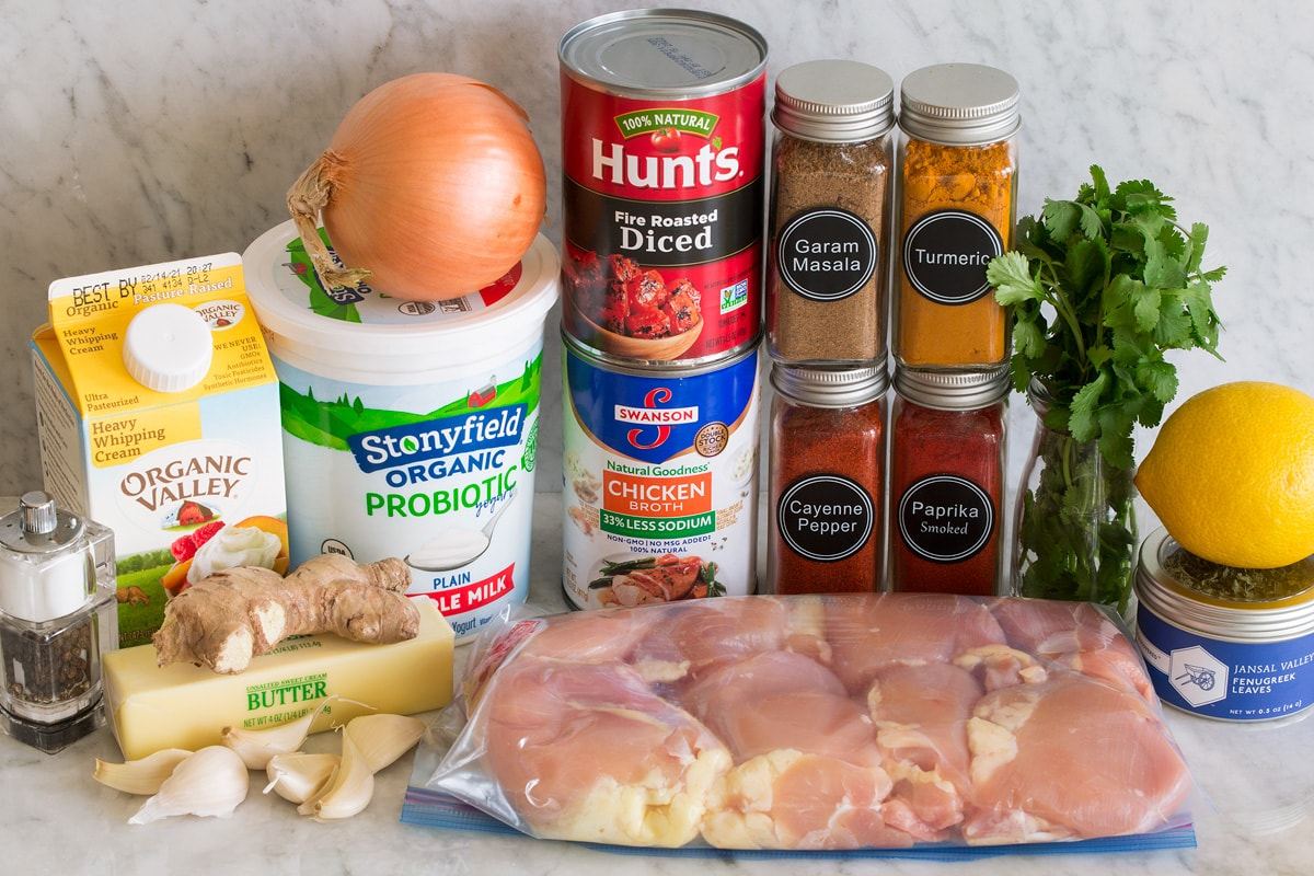 Photo of ingredients used to make butter chicken. Includes chicken thighs, cream, butter, ginger, garlic, salt and pepper, chicken broth, tomatoes, garam masala, turmeric, smoked paprika, cayenne pepper, cilantro, lemon and fenugreek.