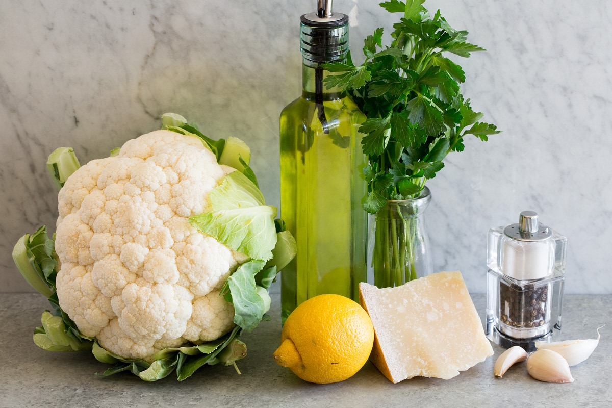 Photo of ingredients used to make cauliflower rice. Includes fresh cauliflower, olive oil, parsley, garlic, parmesan, lemon, salt and pepper.