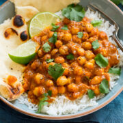 Photo of chickpea curry in a bowl served atop basmati rice with naan bread to the side.