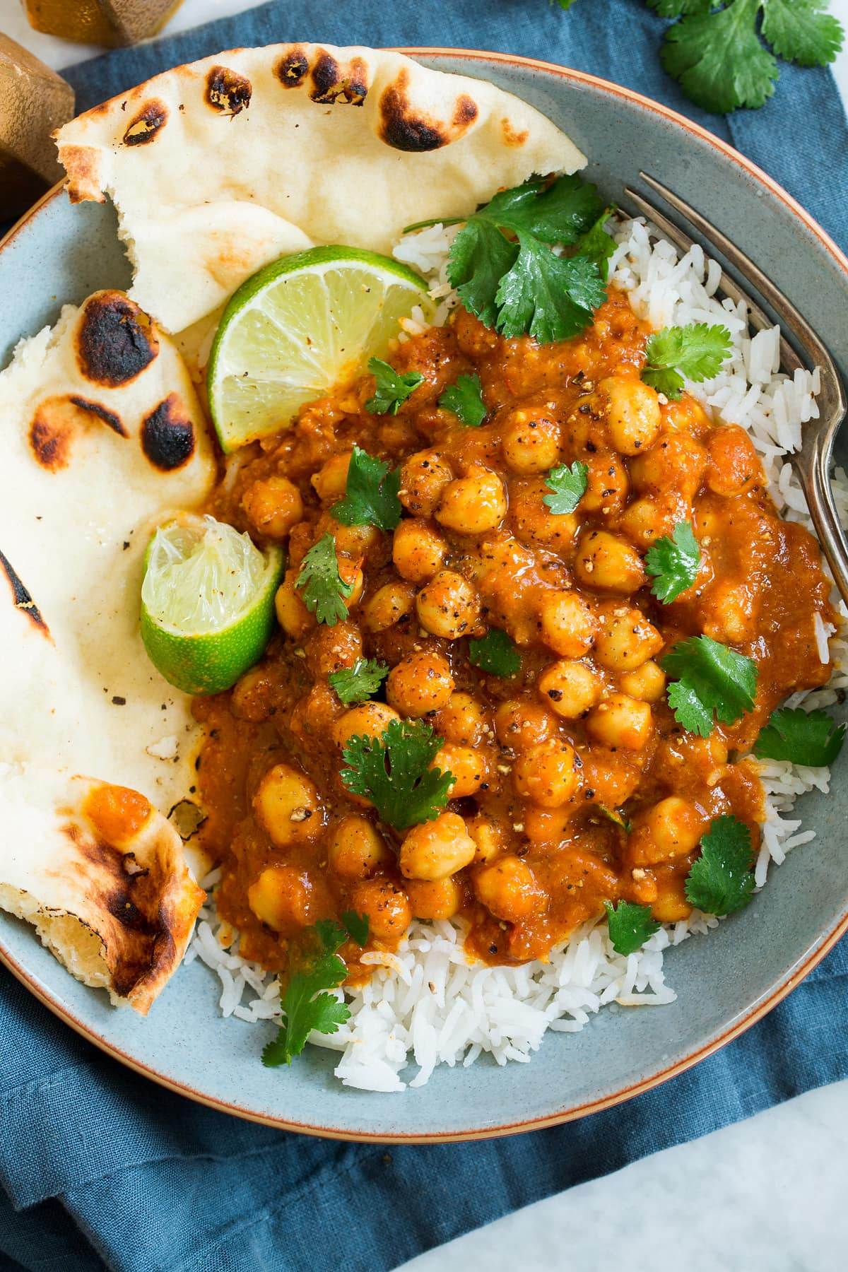 Overhead photo of single serving of chickpea curry with rice, naan, cilantro and limes.