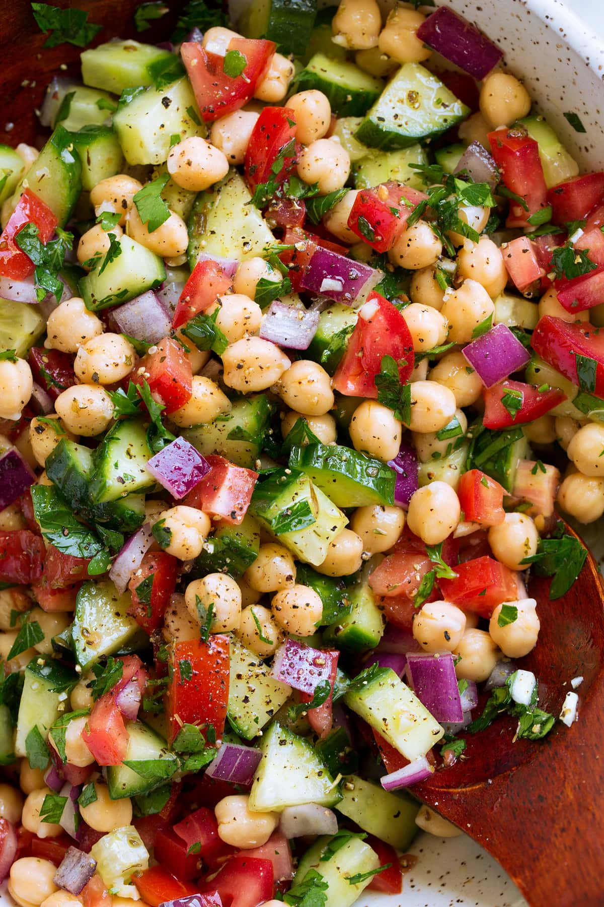 Close up overhead photo of Chickpea Salad with chickpeas, tomatoes, cucumbers, herbs and onion.
