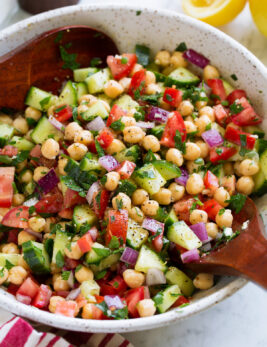 Chickpea Salad shown in a serving bowl with wooden serving spoons.