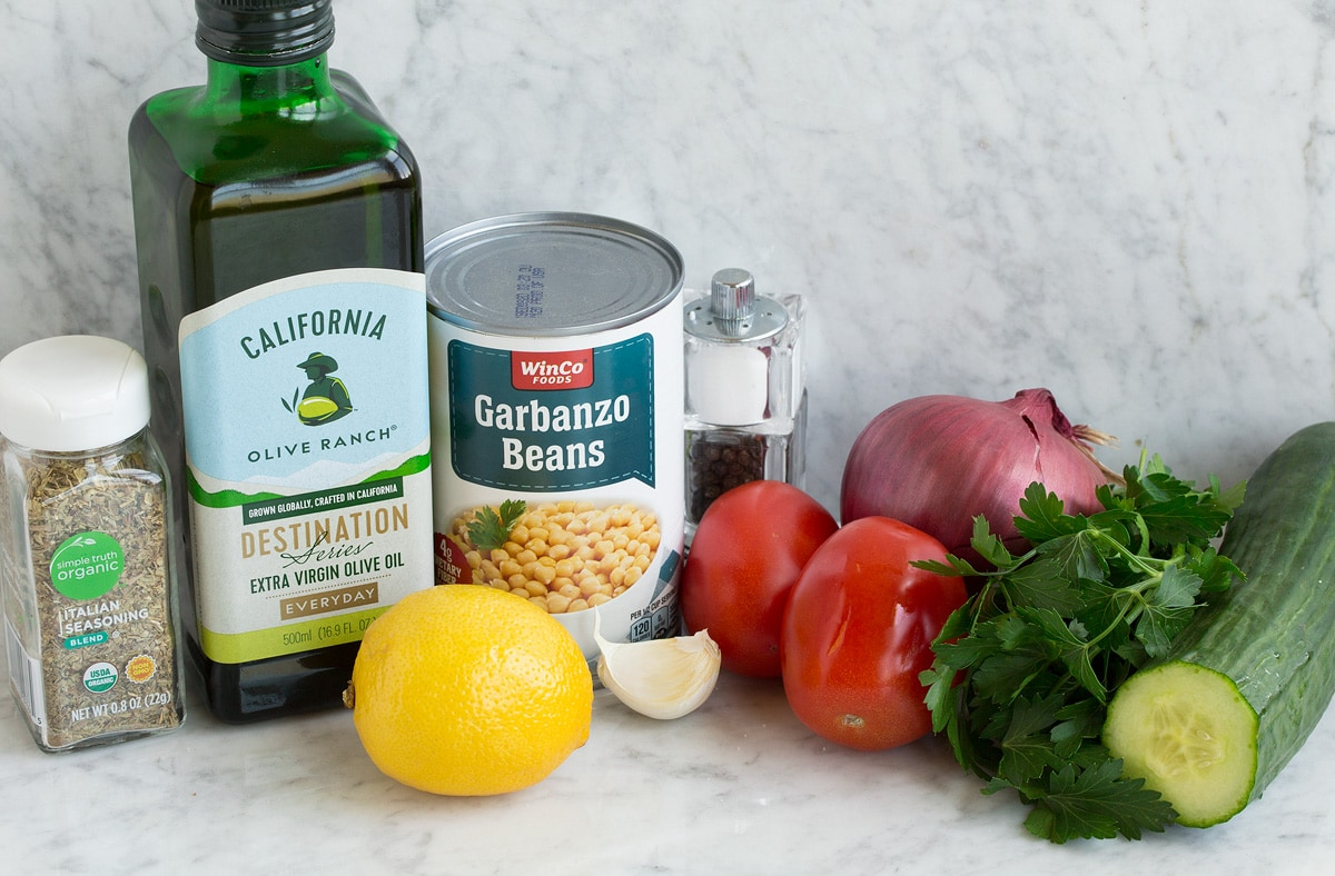 Photo of ingredients used to make chick pea salad. Includes olive oil, chickpeas/garbanzo beans, tomatoes, red onion, parsley, cucumber, garlic and lemon.