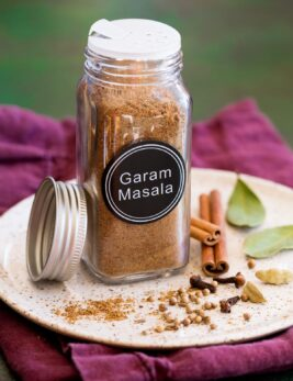 Garam masala spice blend in a glass jar set over a plate with whole spices next to it.