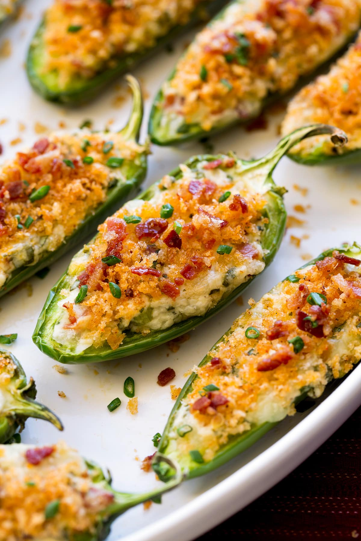 Close up photo of jalapeno poppers on a white serving platter.