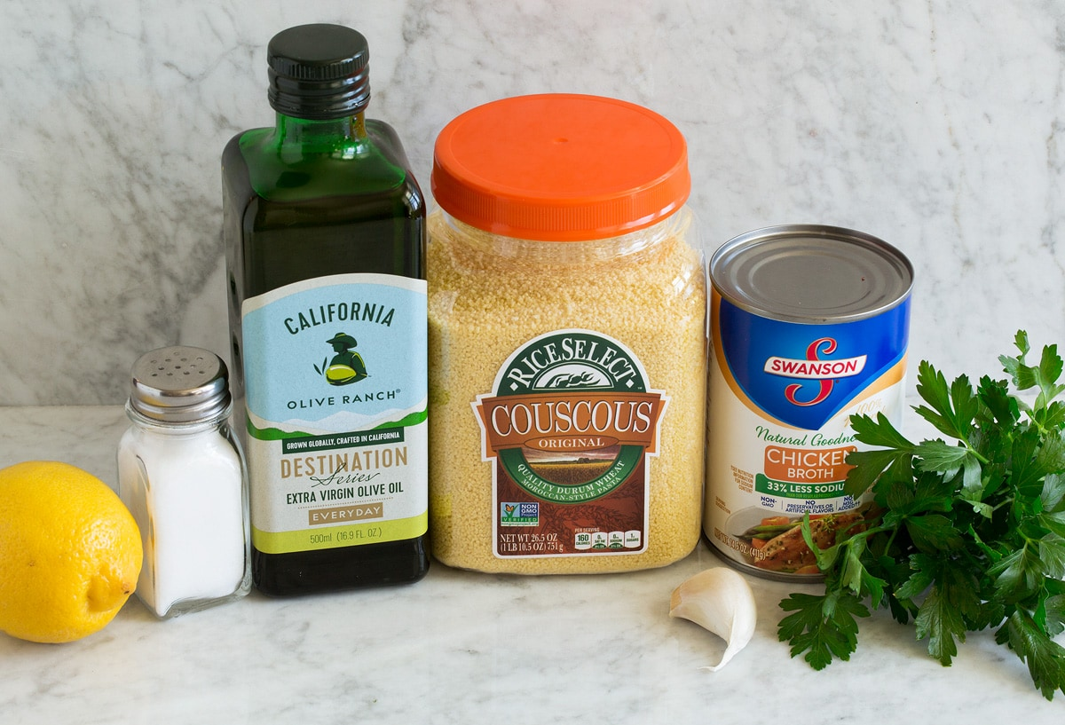 Photo of ingredients used in lemon couscous. Includes moroccan couscous, olive oil, garlic, parsley, chicken broth, lemon, salt.