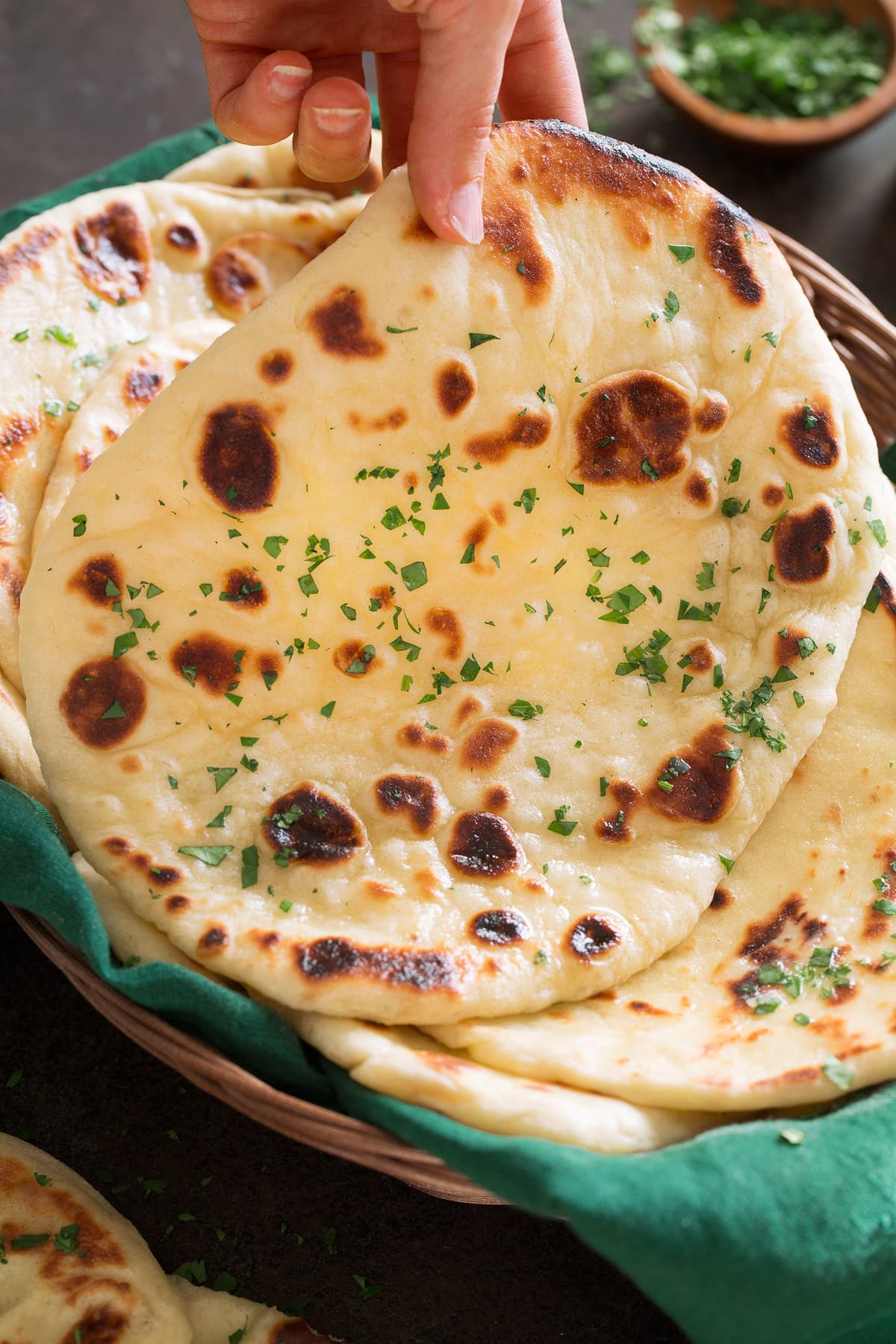 Photo of hand lifting soft naan bread from basket.