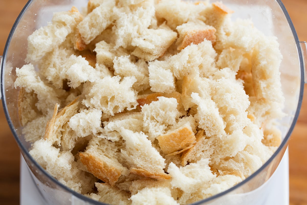 Photo of torn bread pieces in a food processor. This is the first step of making homemade bread crumbs.