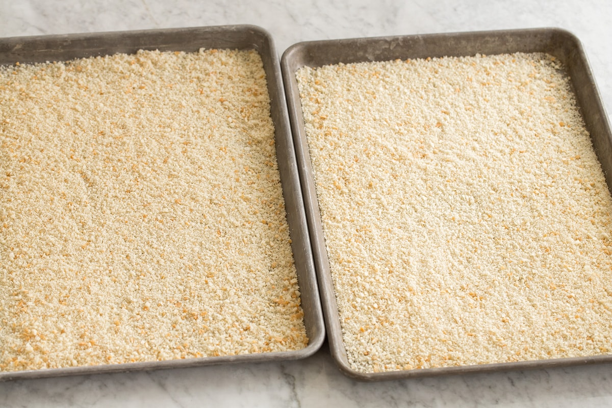 Fine fresh bread crumbs spread on two baking sheets shown before baking. The thirst step of making bread crumbs.