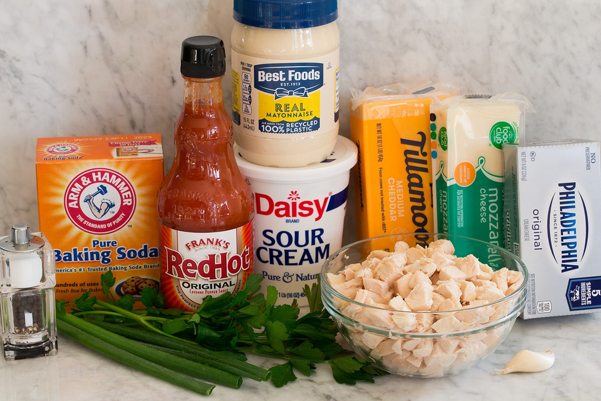 Photos of ingredients for buffalo chicken dip. Includes cooked chicken, buffalo sauce, sour cream, mayonnaise, cheddar cheese, mozzarella cheese, cream cheese, garlic, green onions, parsley, baking soda, salt and pepper.