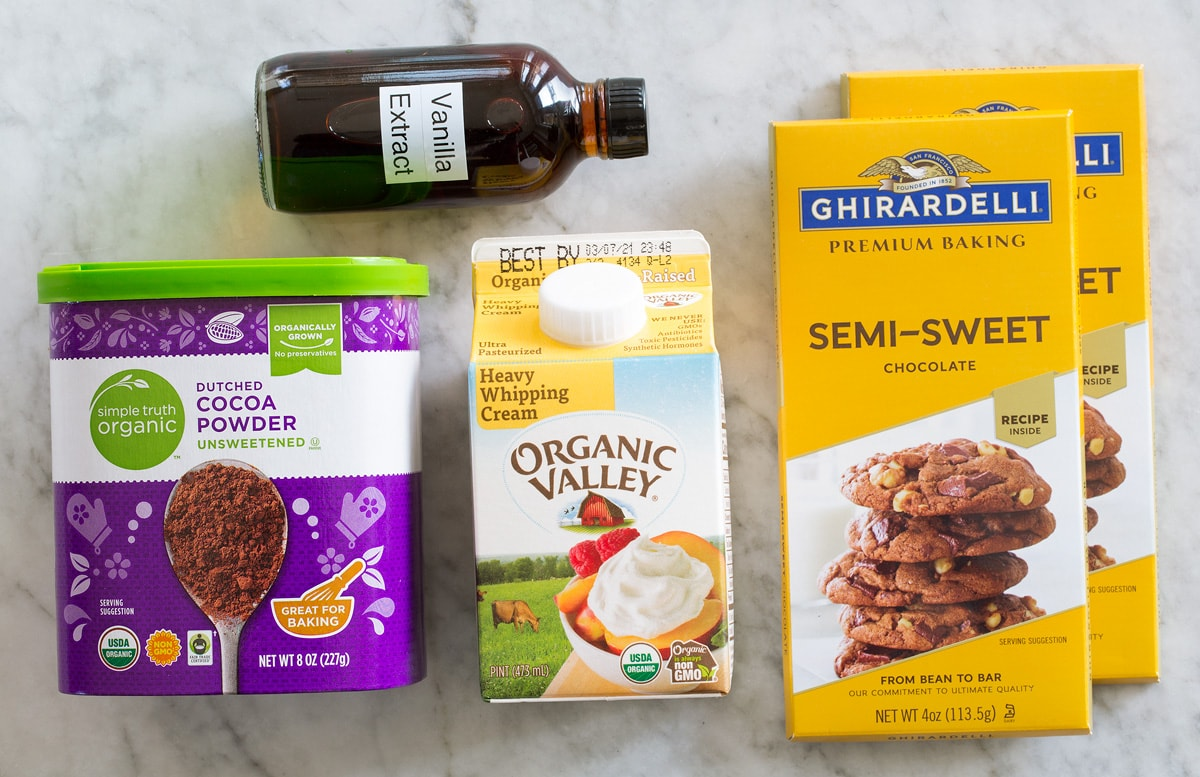 Photo of ingredients used to make homemade chocolate truffles. Includes chocolate bars, heavy cream, vanilla extract, and cocoa powder.