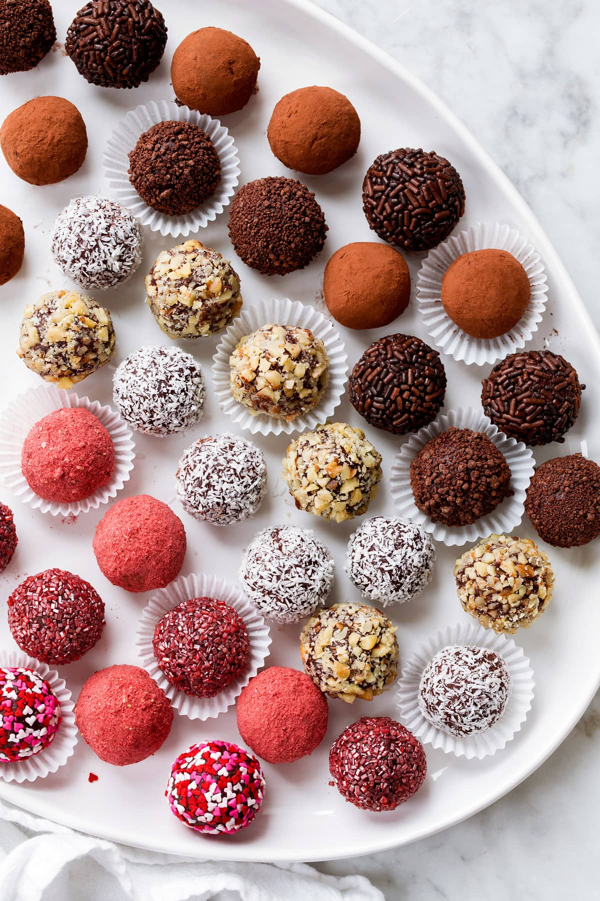 Rows of chocolate truffles coated in different toppings shown on a white oval serving platter.